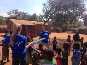 Kiddos playing limbo while the team repairs their village well!